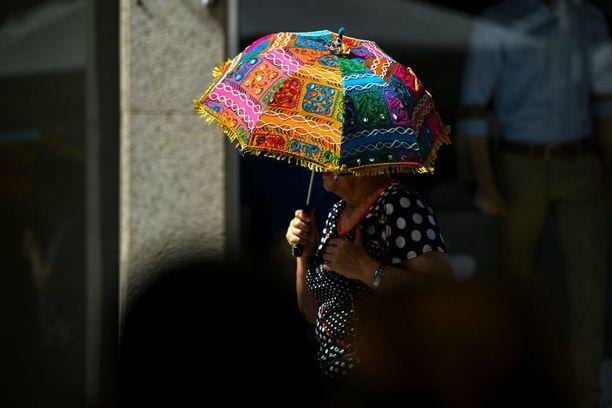 Nainen suojasi kasvonsa päivänvarjon alle Portugalin Bragassa.