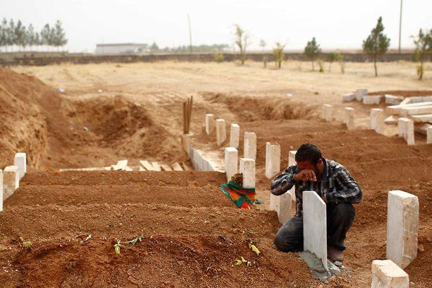 Kurdimies suri Kobanen puolustustaistelussa kuolleen YPG:n taistelijan haudalla lauantaina.