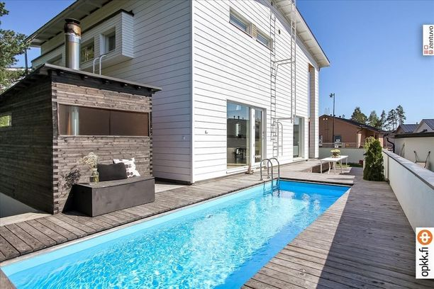 Puulämmitteinen pihasauna ja uima-allas sijaitsevat talon takana omalla terassilla.