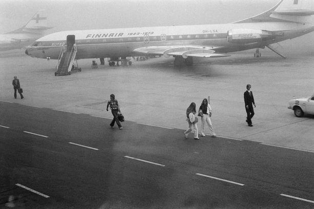 Vuodeksi Yhdysvaltoihin lähteviä vaihto-oppilaita kävelemässä kohti Spear Airin konetta sumuisella lentoasemalla syksyllä 1973. Taustalla Finnairin Super Caravelle OH-LSA. Kuvattu matkustajaterminaalin ikkunasta.