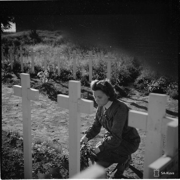 Evakkojen hyvästit kotipaikalleen: Sankarihaudalla. Evakkomatkalle lähtevät isä ja tytär viimeisellä hyvästijättökäynnillä pojan ja veljen sankarihaudalla. Tytär haudalla.