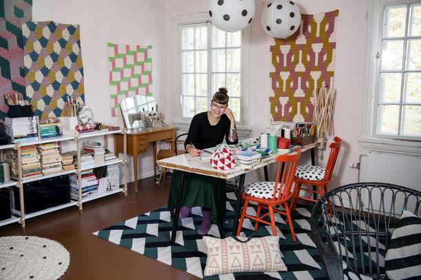 Työhuoneen pöytä oli ensin seinän vieressä, mutta vasta tässä se oli Mollan mielestä oikeassa paikassa. Seinillä Molla suunnittelemia teoksia, lattiaa peittävät hänen suunnittelemansa matot. Rottinkituolit ovat Parolasta.