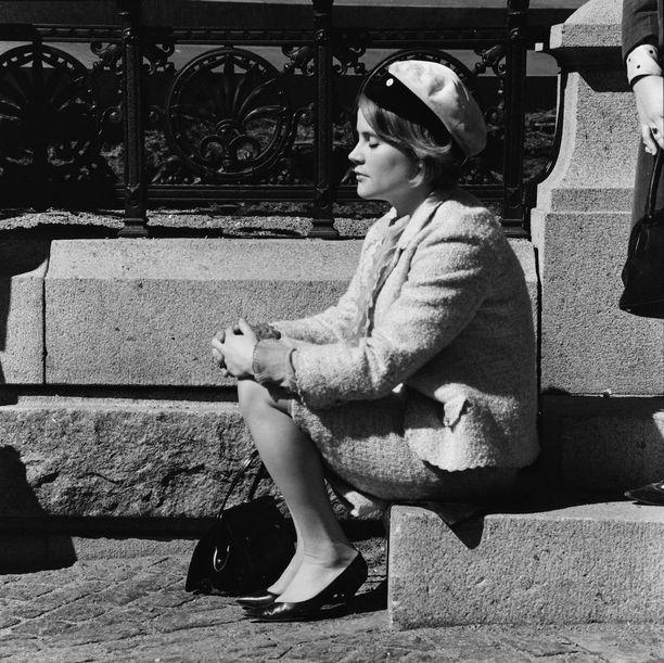 Nainen istuu vapunpäivänä 1966 ylioppilaslakki päässään Aleksanteri II:n patsaan juurella.