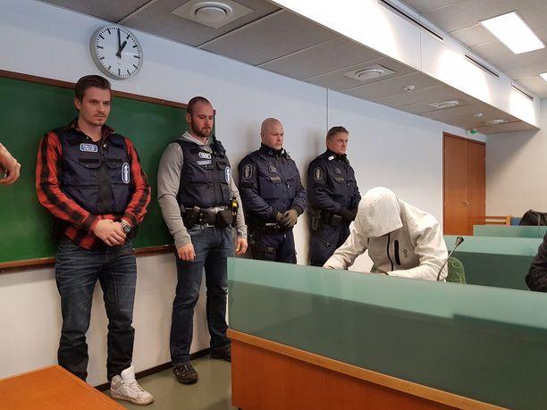 Kolmoissurmasta epäilty mies peitti kasvonsa oikeudessa.
