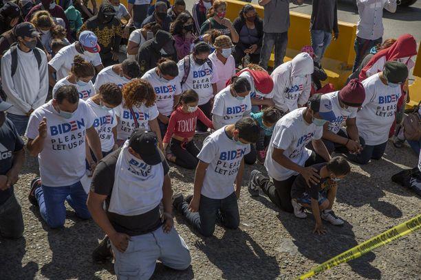 """""""Biden, päästä meidät sisään"""", luki turvapaikkaa hakeneen ihmisjoukon t-paidoissa Meksikon ja USA:n välisellä rajalla kuun alussa."""