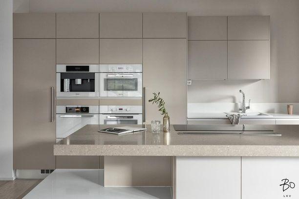 Beige sävy ja vetimettömät kaapit antavat tälle modernille keittiölle harmonisen ilmeen.
