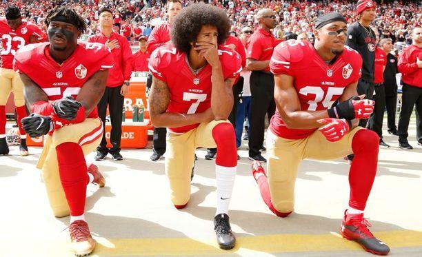 Colin Kaepernick polvistui San Francisco 49ersissa pelatessaan yhdessä joukkuekaveriensa Eli Haroldin ja Eric Reidin kanssa kansallislaulun aikana.