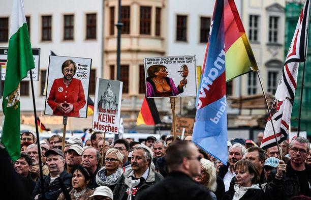 Pegidan ja AfD:n kannattajat pitivät protestissa kylttejä, joissa vastustettiin moskeijoita ja esitettiin Merkel valehtelijana.