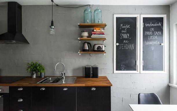 Tämän keittiön trendikäs ilme syntyy suosituista avohyllyistä, tauluista seinällä ja roikkuvasta kattovalaisimesta työtasojen yllä. Rouhea seinä sekin on ajanhengen mukainen.