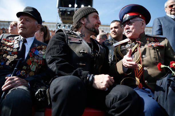 """Yön susien puheenjohtaja, Aleksander Zaldostanov eli """"Kirurgi"""" keskusteli veteraanin kanssa voitonpäivän paraatin yleisössä."""