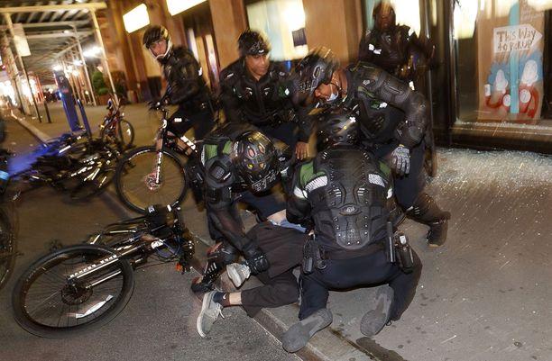 Joukko poliiseja pidättää ulkonaliikkumiskieltoa rikkonutta mielenosoittajaa New Yorkissa keskiviikkona 3.6.