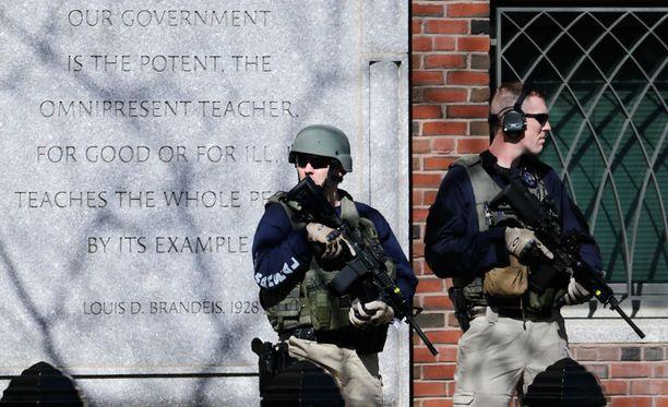 Raskaasti varustautuneet poliisit vartioivat oikeustaloa evakuoinnin jälkeen.