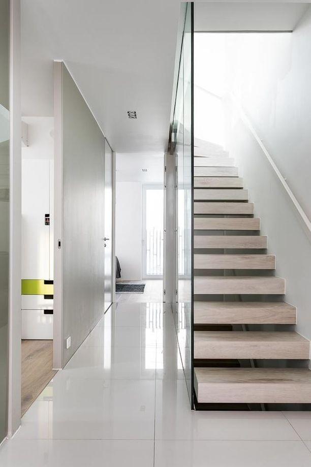 Valo pääsee virtaamaan kapeaan portaikkoon lasiseinän läpi.