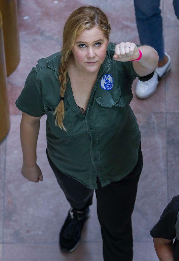 Amy Schumer katsoi suoraan kameraan, kun poliisit saattelivat häntä pois.