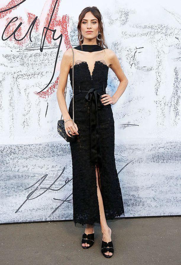 Tyyli-ikoni Alexa Chung valitsi kesäjuhliin mustaa - eikä elegantti mekko ole yhtään liian synkkä, kiitos avonaisen mallin. Huomiomme kiinnittyy kuitenkin asusteisiin. Korvikset ovat aivan ihanat, ja kenkien malli ei voisi olla muodikkaampi. Kaulalle heitetty ohut huivi tuo lookiin vanhan ajan glamouria.