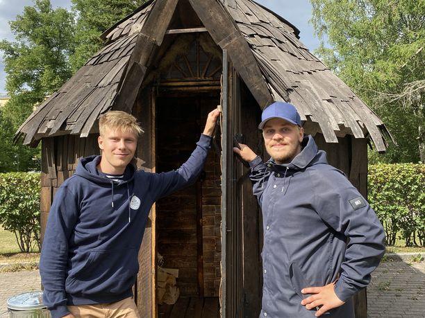 Veikko Airas ja Pyry Paaso hamppusaunan ovella. Päreillä päällystetty sauna on saanut monia lempinimiä: sitä on kutsuttu niin satumökiksi kuin Röllin taloksikin.