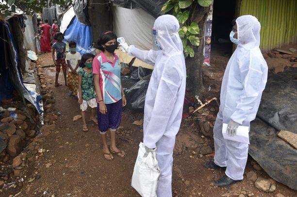 Terveystyöntekijät mittasivat asukkaiden lämpöä Mumbaissa Intiassa 1. heinäkuuta.