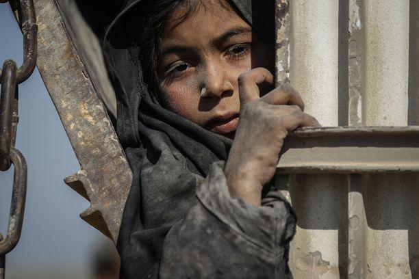 Tyttö katseli ulos siviilejä ja Isis-terroristien perheenjäseniä evakuoineesta kuorma-autosta keskiviikkona.
