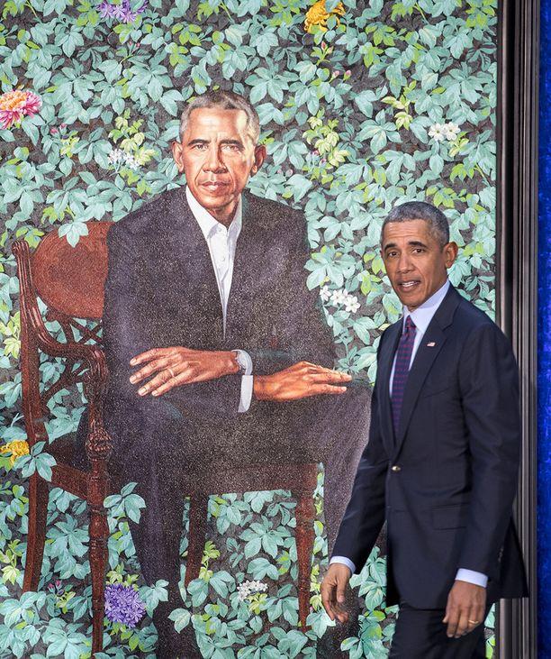Barack Obama istuu muotokuvassa puutarhassa.