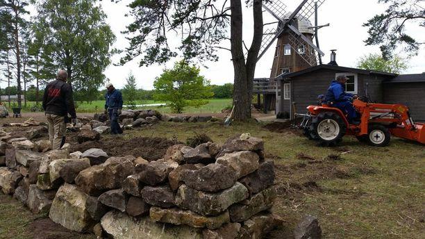 Kuvassa rakennetaan kiviaitaa tontin vanhoista graniittikivistä.