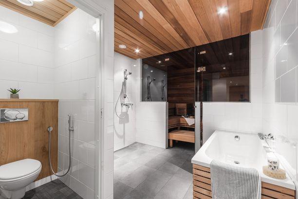 Tässä kylpyhuoneessa sauna kätkeytyy kauniin lasiseinän taakse. Katossa on raikkaat led-lamput ja puupinnat viimeistelevät ylellisen tunnelman.