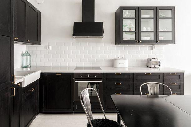 Valkoisen ohella mustat keittiöt ovat suomalaisten suosikkeja. Tämän keittiön tyyli on hyvin klassinen. Lasiovelliset yläkaapit keventävät keittiön ilmettä.