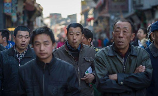 Kiinassa ollaan havahduttu väestökriisiin. Kuvassa joukko miehiä käveli kadulla Pekingissä.