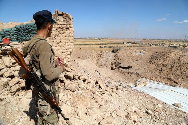 Kurditaistelija katsoi kohti Turkin rajaa, kun taistelijat siirtyivät lähelle Turkin rajaa syyrialaisessa Ras El Ainin kylässä maanantaina.