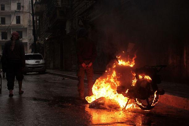 Syyrialaiset seisoivat eilen palavan moottoripyörän vieressä al-Mashhadin kaupunginosassa Aleppossa. Asukkaat polttivat useita tavaroita ennen kuin Syyrian joukot etenivät kaupunkiin.