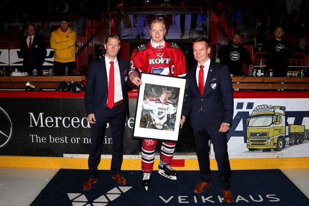 HIFK:n urheilujohtaja Tobias Salmelainen (vas.) ja toimitusjohtaja Jukka Valtanen (oik.) palkitsivat Lennart Petrellin 500 liigaottelun johdosta. Petrell on pelannut kaikki pelit IFK-paidassa.