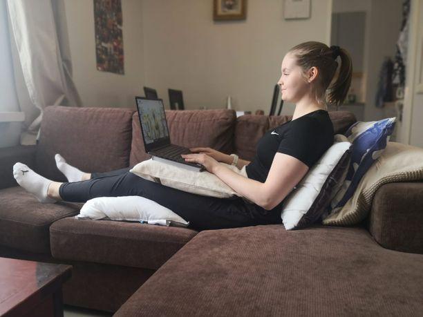 Fysioterapiaa opiskeleva Maria Paul näyttää, miten ergonominen työasento sohvalta löytyy.