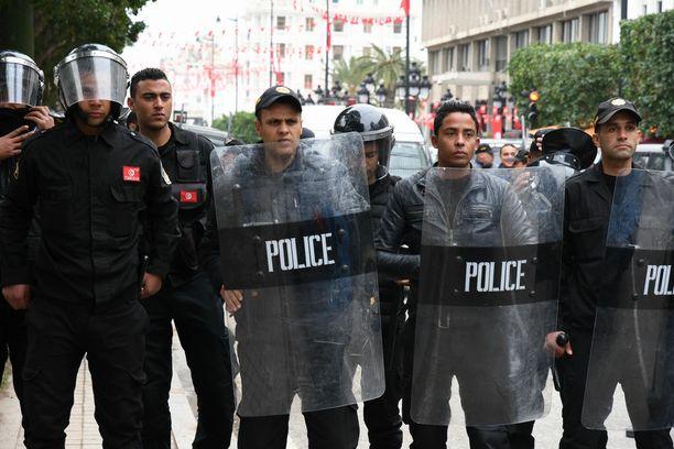 Poliisin rivistöjä tiistain mielenosoituksissa pääkaupunki Tunisissa.