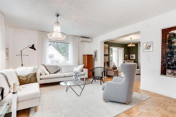 Vaalean kodin tv-huone on maalattu murretulla oliivinvihreällä.