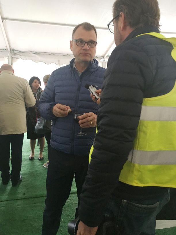 Sipilä antoi kommentteja medialle rennosti viinilasi kädessä.