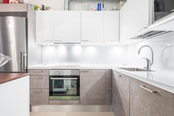 Asunto on lähes uudenveroinen, mikä näkyy modernissa valkopainotteisessa keittiössä.