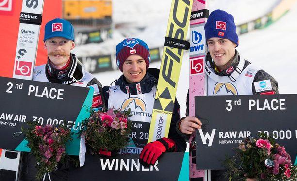 Kamil Stoch (keskellä) juhli maailmancupin kokonaiskilpailun voittoa. Kuvassa vasemmalla voittoon hypännyt Robert Johansson ja oikealla toiseksi ponnistanut Andreas Stjernen.