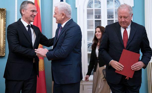 NATO:n pääsihteeri Jens Stoltenberg (vas.) ja Montenegron pääministeri Dusko Markovic kättelevät seremoniassa, jossa jäsenyys vahvistettiin.