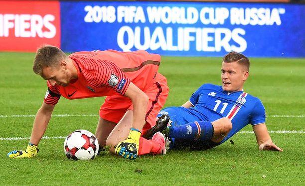 Lukas Hradecky kaivaa pallon Islannin Alfred Finnbogasonin jaloista.