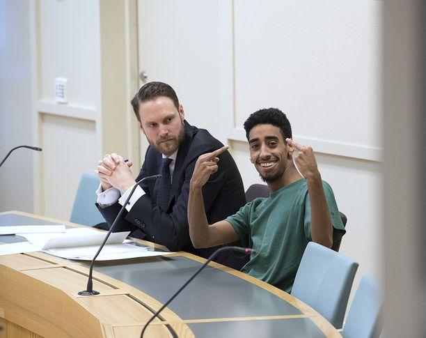 Elinkautiseen tuomittu Fouad Saleh näytti oikeudessa lehtikuvaajalle käsimerkkejä.