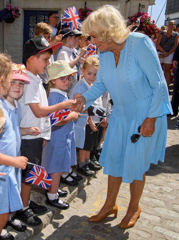 Camilla kumartui lapsia lähemmäs näitä kätellessään.