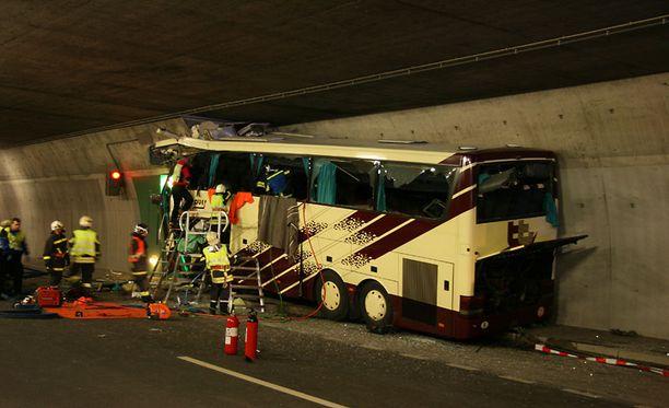Valais'n kantonin poliisin julkaisemassa kuvassa bussi on vielä kiinni hätäuloskäynnin seinässä, johon se törmäsi.