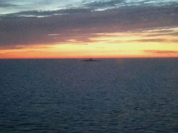 Laivan oikealla puolella näkyi selkeä sukellusveneen siluetti.