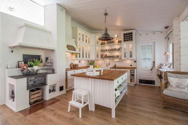 Iso saareke ja puuhella tekevät keittiöstä kodikkaan.