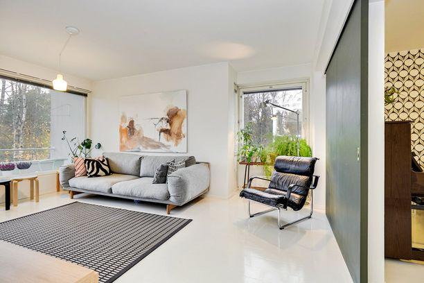 Huoneen harmoninen kokonaisuus lumoaa. Sieltä löytyy Yrjö Kukkapuron suunnittelema Remmi-tuoli, Artekin valaisin sekä jakkarat, Woodnotesin New York-matto ja Marimekon tyynyjä sohvalta.