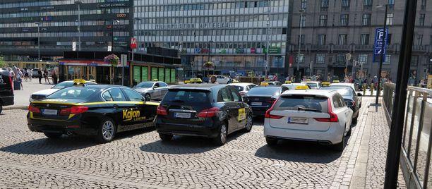 Helsingin Elielinaukion taksiasemalla näkyi heinäkuisena perjantaina lähestulkoon ainoastaan Taksi Helsingin autoja. Jonossa oli vain yksi Kajonin auto.