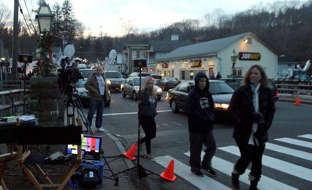 Kamerat ja reportterit rantautuivat Newtownin kaupunkikuvaan.