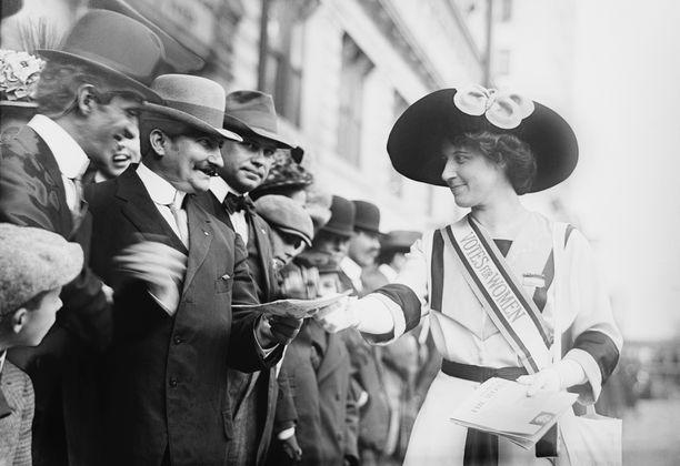 Inez Milholland myy feminististä lehteä suffragettiparaatin sivustakatselijoille. Kuvan on arvioitu ajoittuvan vuosille 1913-1916.
