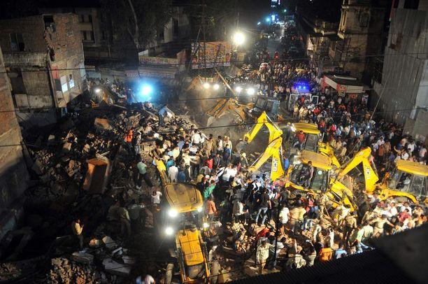 Pelastustyöntekijät etsivät ihmisiä raunioista Intiassa romahtaneen hotellin raunioista.