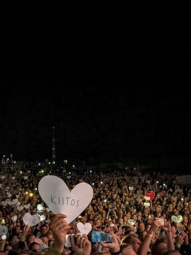 Sadat fanit heiluttivat valkoisia sydämenmuotoisia kylttejä, joissa luki Kiitos.