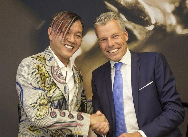 Hotellin rakennuttaja Stephen Hung (vas.) kättelee Rolls-Roycen toimitusjohtajaa Torsten Müller-Ötvösta kaupantekotilaisuudessa.